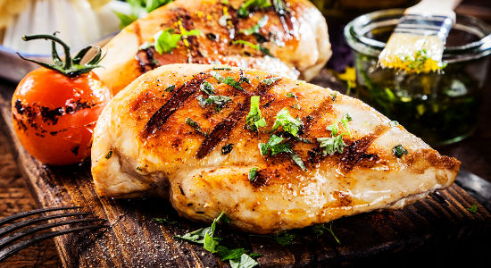 Marinated grilled healthy chicken breasts cooked on a summer BBQ
