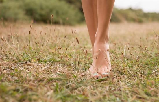 Donna cammina a piedi nudi sull'erba