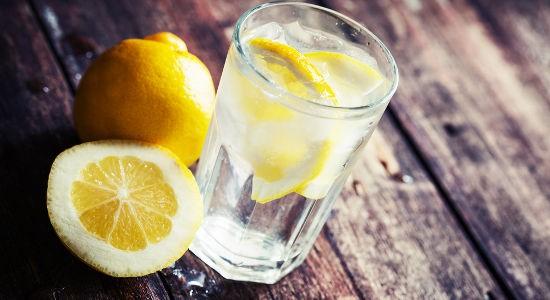 Lemonade with fresh lemon on wooden background