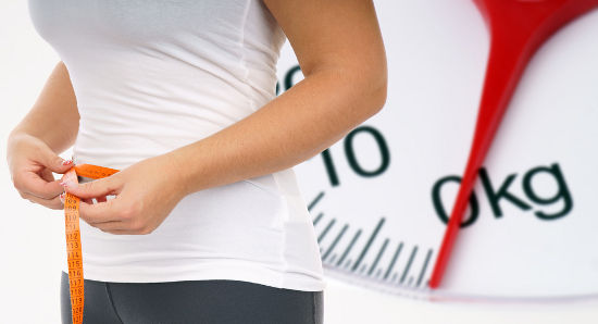 Woman with bathroom scale and measuring tape / diet
