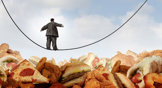 Overweight diet danger concept as an obese man walking on a tightrope high wire over greasy junk food as a metaphor for dieting risk and the challenges of eating disorders resulting in obesity