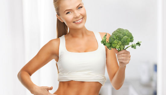 beautiful woman pointing at her abs and holding broccoli