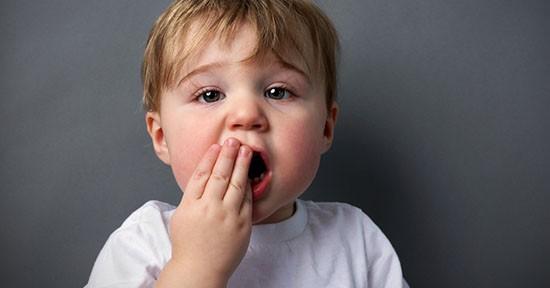 Bambino porta le mani alla bocca