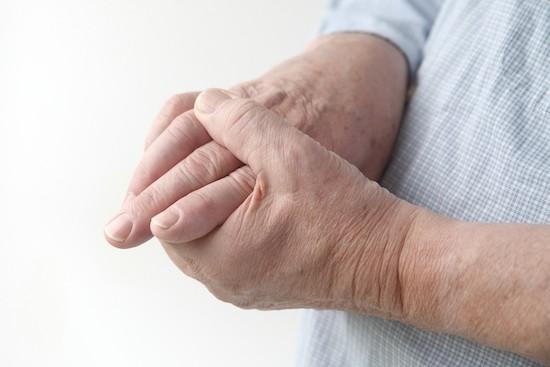 Uomo con dolore alle articolazioni delle mani
