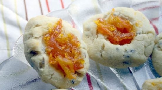 A pair of lavender shortbread thumbprint cookies with orange marmalade