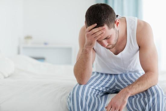 Uomo a letto con mal di testa