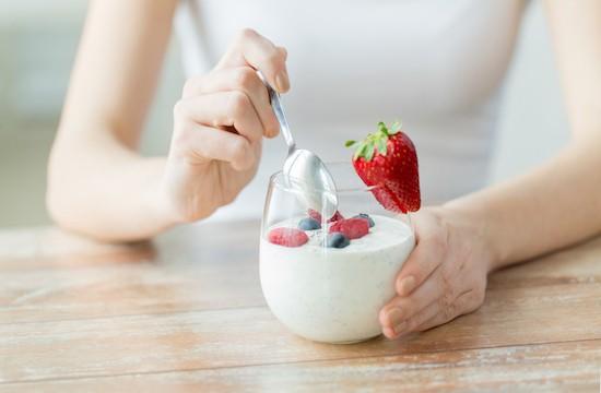 Donna mangia uno yogurt