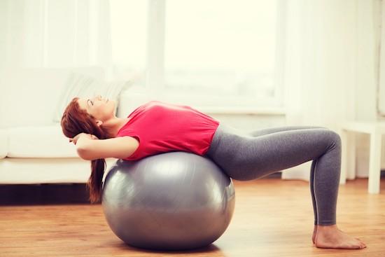 Pilates, donna sdraiata su palla