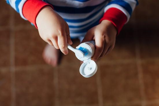 Bambino con spazzolino e dentifricio
