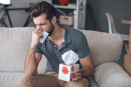 Uomo soffia naso per allergia