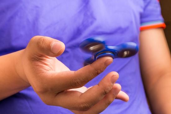 Ragazzo gioca con un fidget spinner