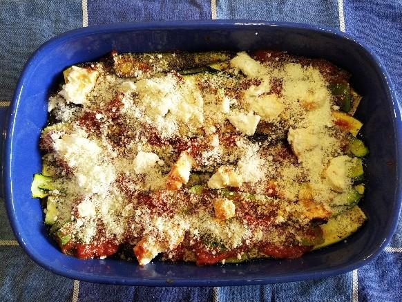 Disponete le zucchine in modo omogeneo e cospargetele con salsa di pomodoro, cubetti di formaggio e parmigiano. Continuate ad alternare gli strati in questo modo, fino a esaurimento degli ingredienti.